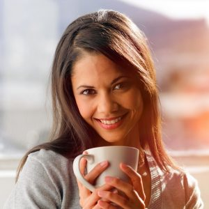 Woman drinking coffee at home with sunrise streaming in through window and creating flare into the lens.