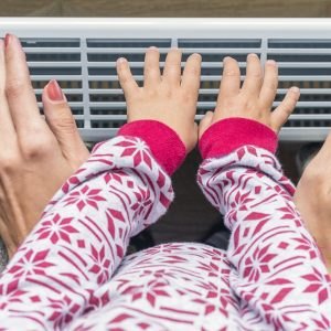 Woman and child warm up hands over electric heater.