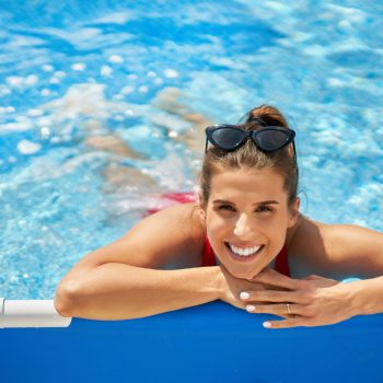 Picture of an attractive young woman relaxing on swimming pool in the backyard